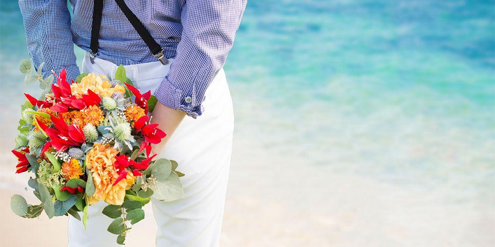 海辺で花束を持つ男性