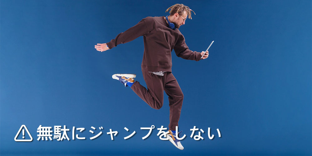 スマホを持ちながらジャンプする男性