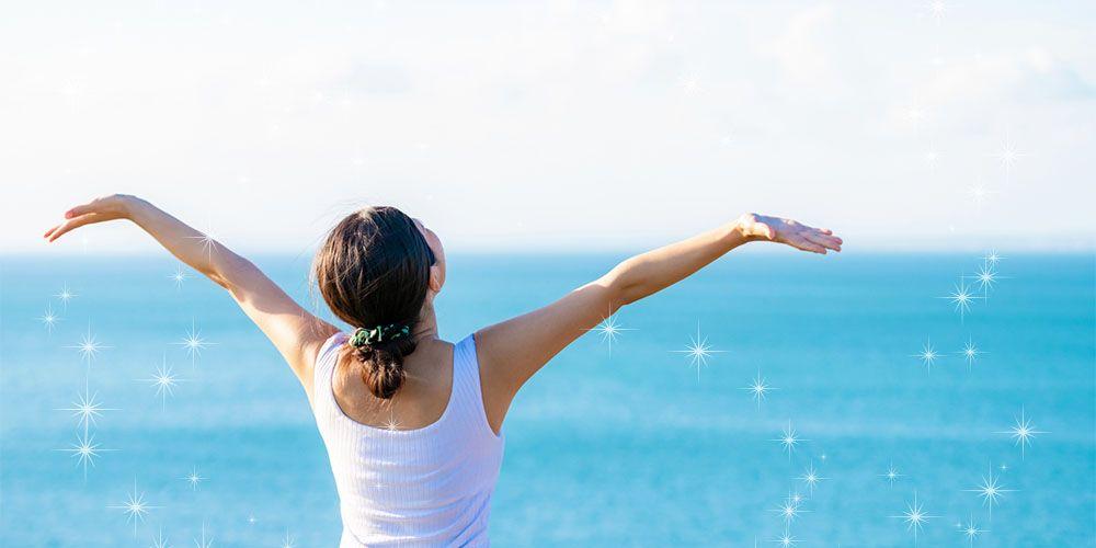 両手を広げる海辺の女性