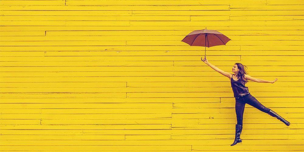 傘をさして軽やかに跳ねる女性